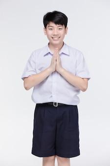 Il ragazzo asiatico del bambino in uniforme dello studente, comportandosi sawaddee significa ciao.