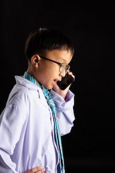 Il ragazzo asiatico imita l'adulto con lo smartphone