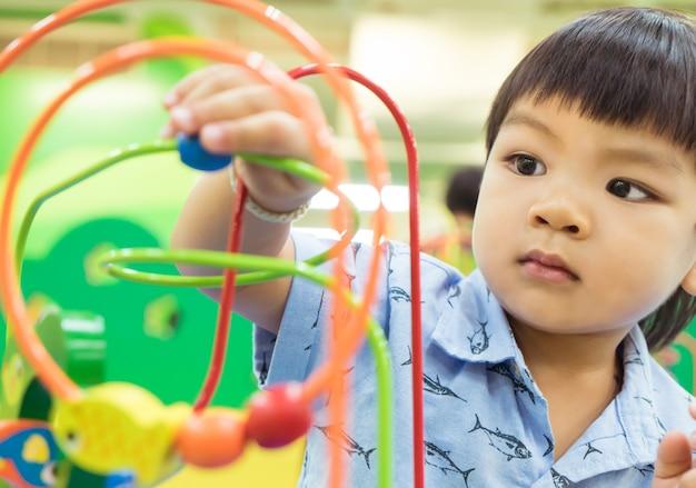 Il ragazzo asiatico sta giocando con il giocattolo educativo