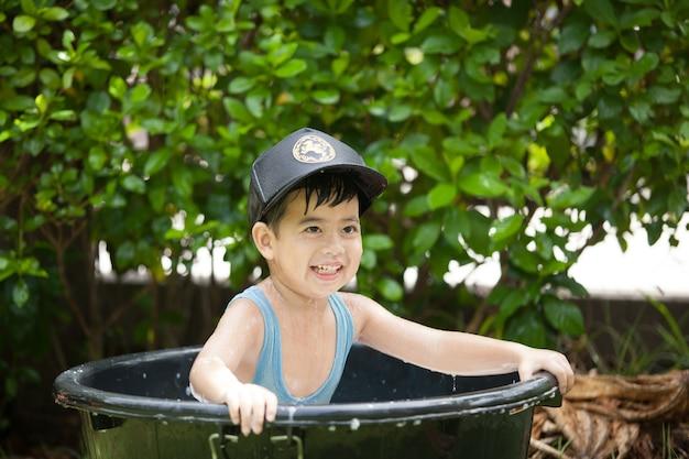 Il ragazzo asiatico sveglio si diverte giocando in acqua da un tubo flessibile un giorno di estate soleggiato caldo