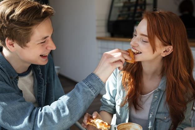 Il ragazzo attento nutre la sua ragazza
