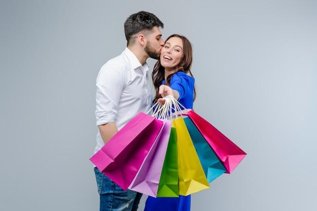 Il ragazzo bacia la ragazza con i sacchetti della spesa variopinti