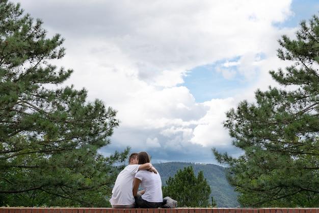 Il ragazzo bacia una ragazza sul bordo di un alto edificio sullo sfondo delle montagne.