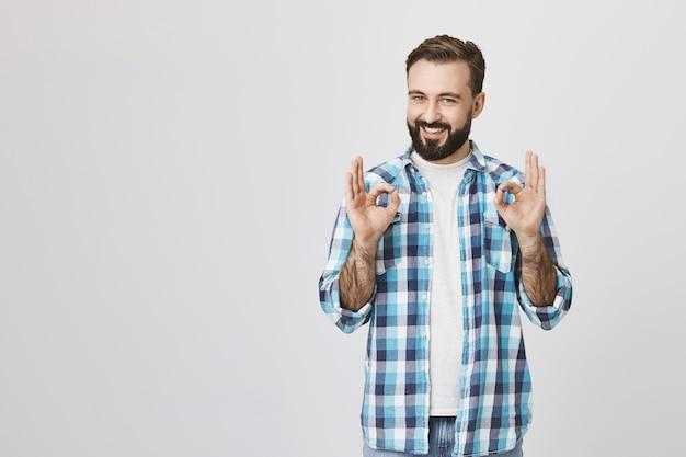 Il ragazzo barbuto adulto soddisfatto mostra i gesti giusti