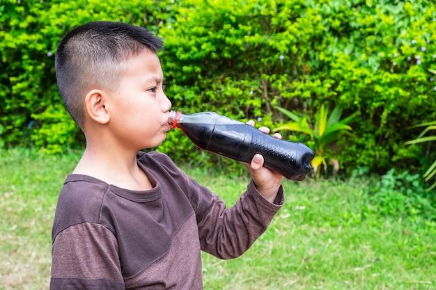 Il ragazzo beve acqua di cola dalla bottiglia.