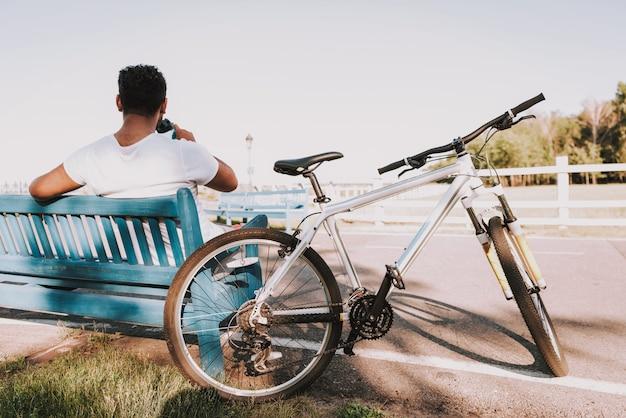 Il ragazzo beve l'acqua sulla panchina del parco accanto alla bicicletta.