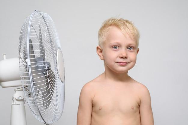 Il ragazzo biondo abbastanza sorridente con il torso nudo sta vicino ad un ventilatore. concetto di estate