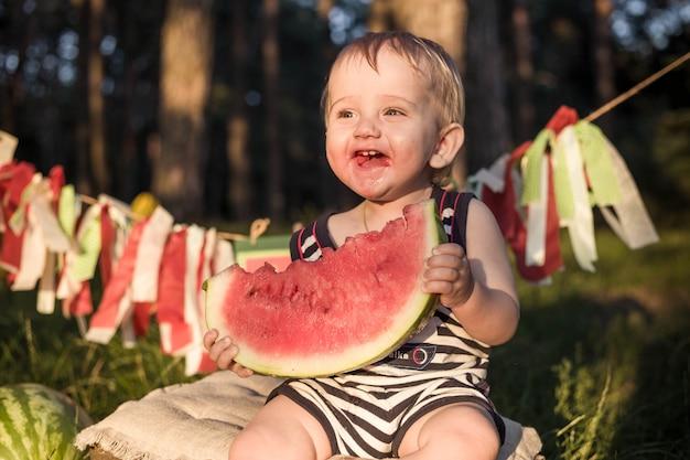 Il ragazzo biondo si siede circondato dalle angurie un giorno di estate