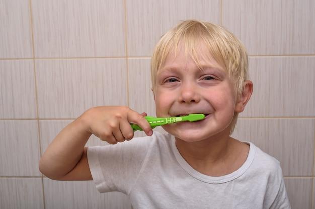 Il ragazzo biondo sorridente pulisce diligentemente i suoi denti nel bagno. abitudini salutari