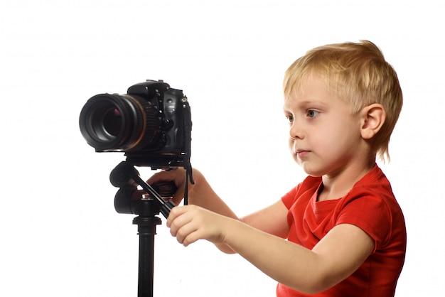 Il ragazzo biondo spara il video sulla macchina fotografica di dslr. vista frontale. , isolato