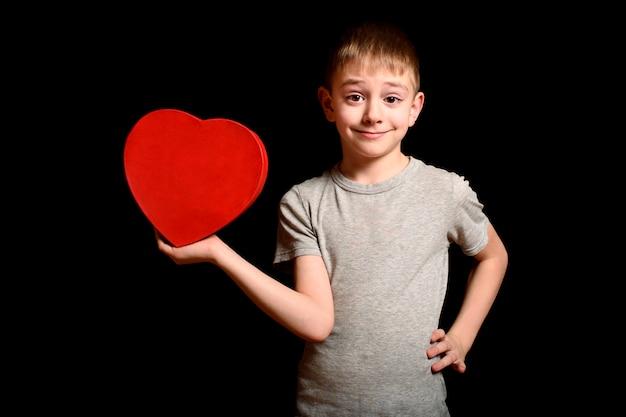 Il ragazzo biondo tiene una scatola a forma di cuore rossa nella sua mano su spazio nero. amore e concetto di famiglia