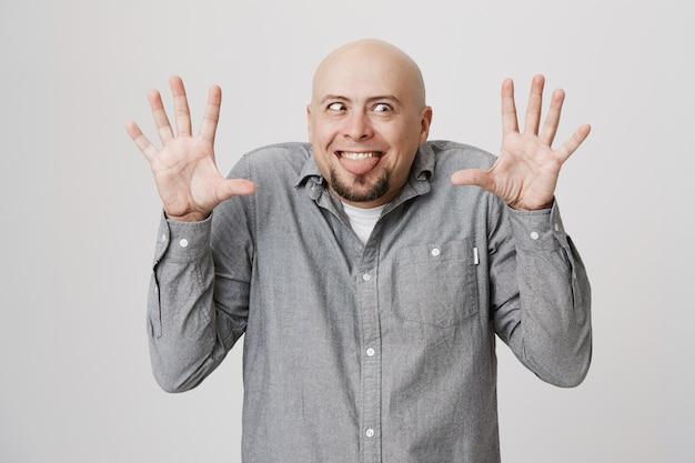 Il ragazzo calvo divertente e sciocco mostra facce buffe e alza le mani