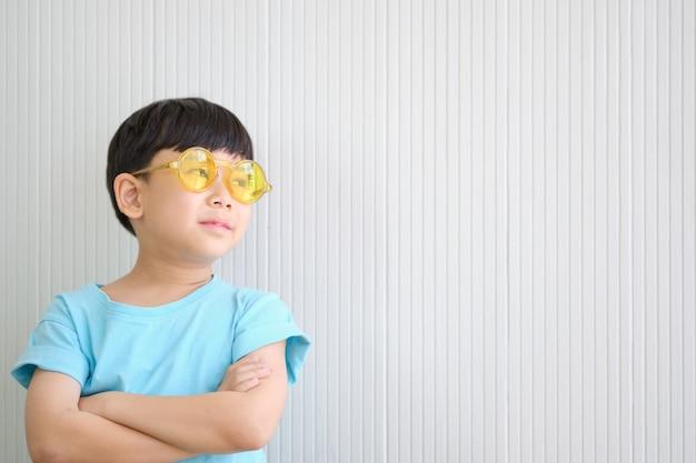 Il ragazzo carino asiatico sta sognando ad occhi aperti mentre indossa occhiali da sole gialli