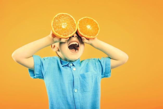 Il ragazzo carino felice si diverte a giocare con l'arancia della frutta