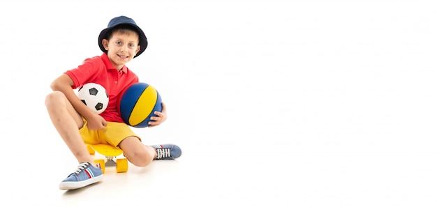 Il ragazzo caucasico dell'adolescente si siede su un penny giallo con pallacanestro e palloni da calcio e sorrisi