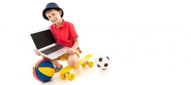Il ragazzo caucasico dell'adolescente si siede su un penny giallo con palloni da basket e da calcio e mostra il suo computer portatile