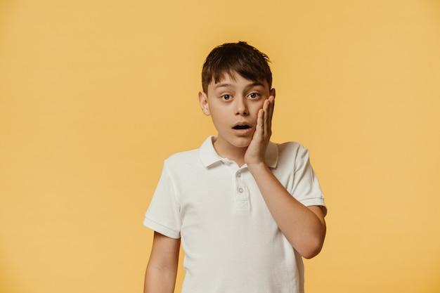 Il ragazzo caucasico scioccato scioccato in maglietta bianca tiene la mascella caduta, tocca la guancia con la mano, sussulta per l'eccitazione, fissa con gli occhi incavati, isolato su un muro giallo, ha un'espressione senza speranza.