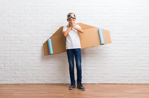 Il ragazzo che gioca con le ali dell'aeroplano del cartone sulla sua parte posteriore che ride