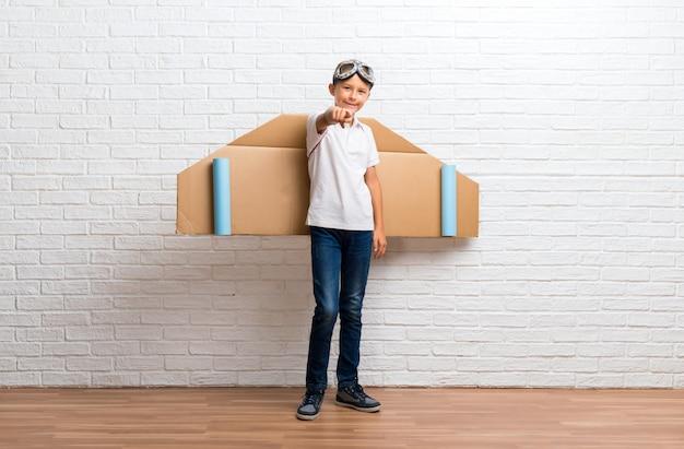 Il ragazzo che gioca con le ali dell'aeroplano del cartone sulla sua parte posteriore indica il dito voi