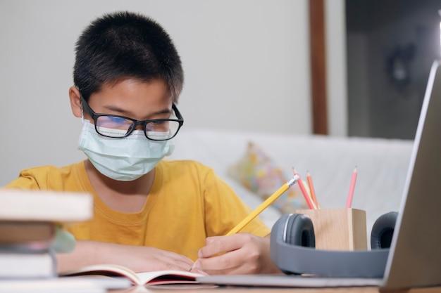 Il ragazzo che indossa le maschere di protezione studia online a casa.