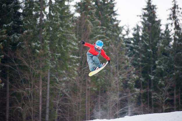 Il ragazzo che salta e tiene una mano sullo snowboard