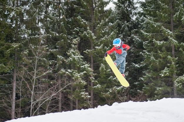 Il ragazzo che salta sullo snowboard