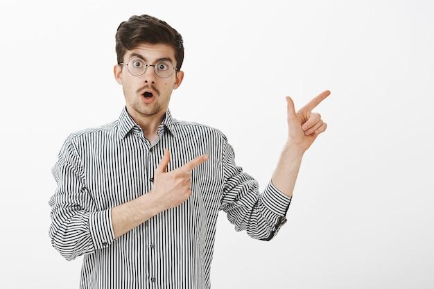 Il ragazzo chiede il permesso di andare con i ragazzi. ritratto del modello maschio europeo ordinario eccitato con barba e baffi, indicando con le pistole del dito a destra e parlando, suggerendo di andare in direzione