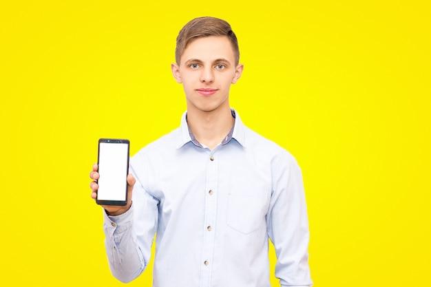 Il ragazzo con la camicia blu pubblicizza il telefono isolato su uno sfondo giallo