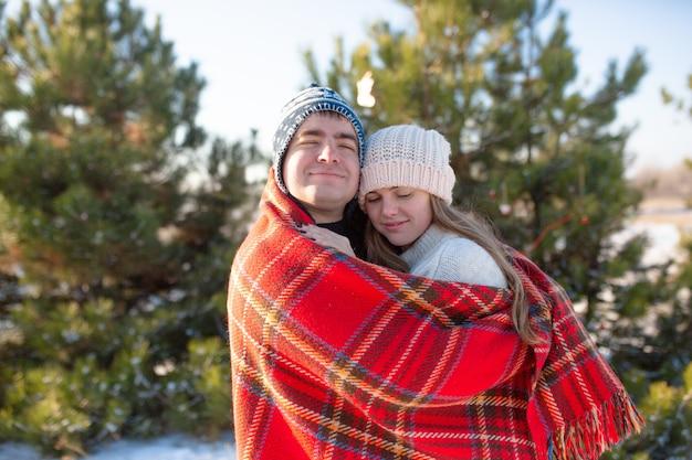 Il ragazzo con la coperta scozzese rossa avvolge la ragazza in modo che si riscaldi