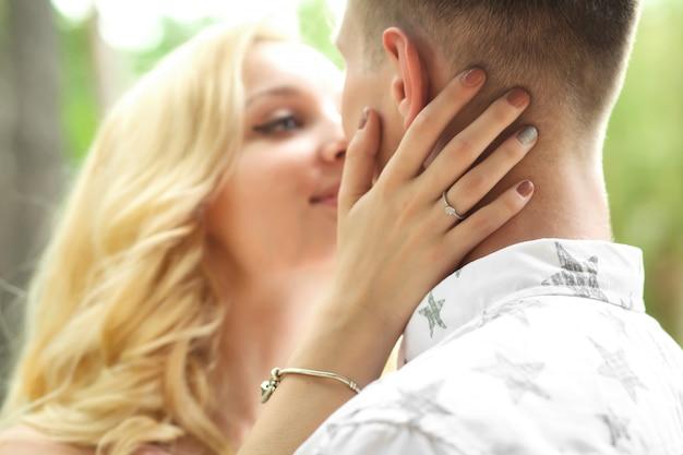 Il ragazzo con la donna abbraccia e bacia. un appuntamento romantico in una pineta, ama la coppia di una coppia adorabile