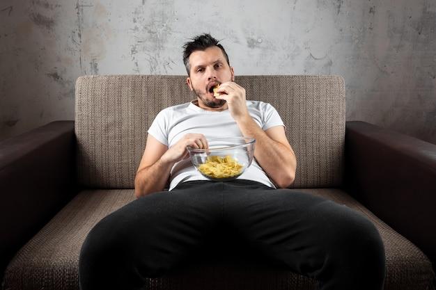 Il ragazzo con la maglietta è sdraiato sul divano, mangia patatine e guarda un canale sportivo