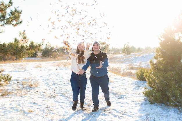 Il ragazzo con la ragazza lancia coriandoli nella foresta invernale