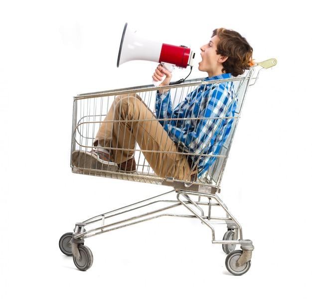 Il ragazzo con un megafono in un carrello della spesa