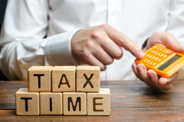 Il ragazzo conta sulla calcolatrice il pagamento dell'imposta necessaria. tassazione, imposta sul reddito