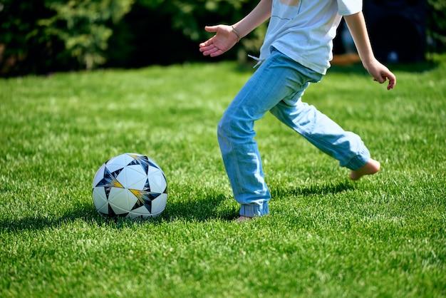 Il ragazzo corre per un pallone da calcio sul prato senza scarpe