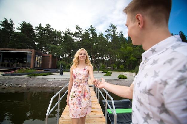 Il ragazzo dà la mano alla ragazza, aiuta a salire sulla barca sul molo