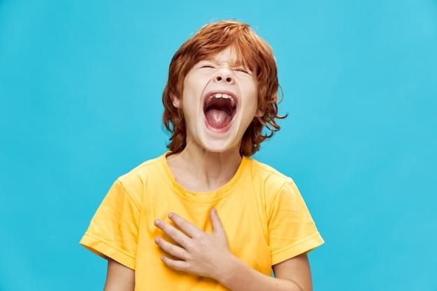 Il ragazzo dai capelli rossi espressivo grida con la bocca spalancata su un blu
