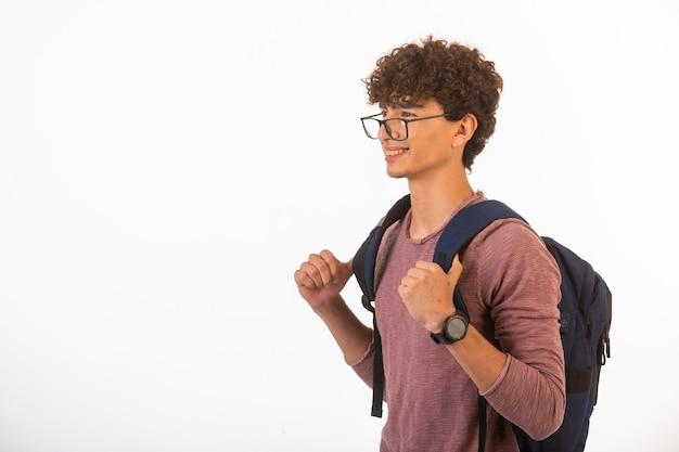 Il ragazzo dei capelli ricci con gli occhiali optique che tiene il suo zaino è felice e gioioso.