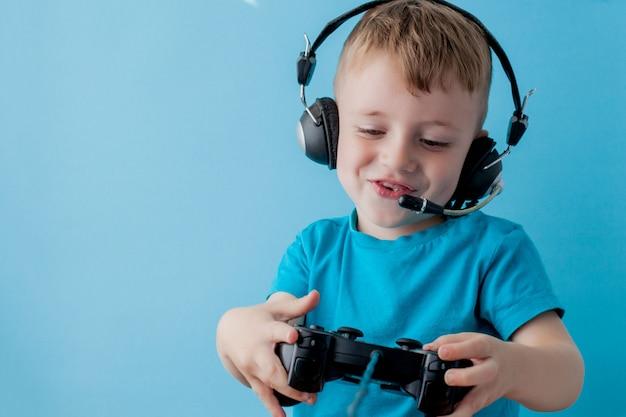 Il ragazzo del bambino 2-3 anni che indossa i vestiti blu tiene la leva di comando a disposizione per i giochi sul ritratto blu dei bambini della parete. concetto di lifestyle di infanzia di persone. mock up copia spazio