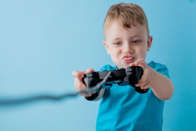Il ragazzo del bambino 2-3 anni che indossa i vestiti blu tiene la leva di comando a disposizione per il ritratto blu dello studio dei bambini del fondo del gameson. concetto di lifestyle di infanzia di persone. mock up copia spazio