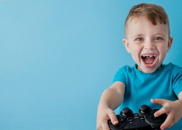 Il ragazzo del bambino che indossa i vestiti blu tiene la leva di comando a disposizione per i giochi. concetto di lifestyle di infanzia di persone. mock up copia spazio
