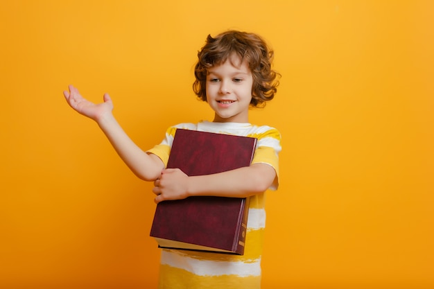 Il ragazzo della scuola sorride, alza la mano e tiene il grande libro