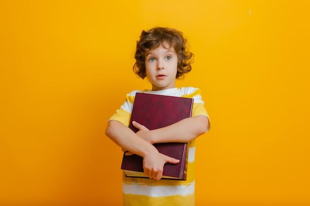 Il ragazzo della scuola sorride e tiene il grande libro