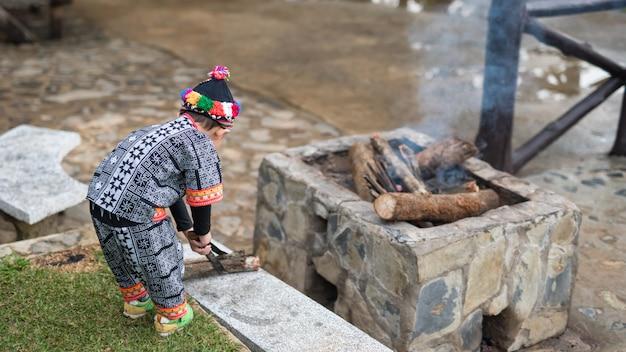 Il ragazzo della tribù della collina fa il fuoco di accampamento per impedire il freddo