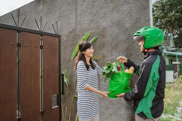 Il ragazzo delle consegne sta consegnando generi alimentari alla donna