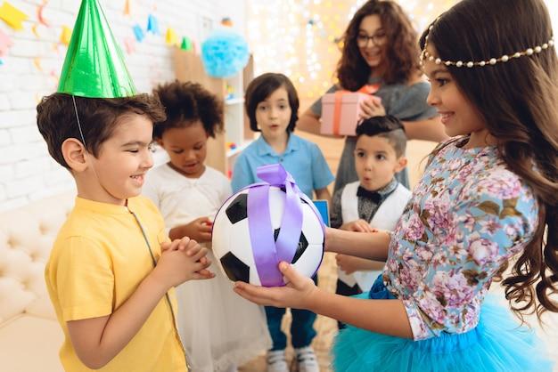 Il ragazzo di compleanno riceve la palla di calcio come regalo di compleanno