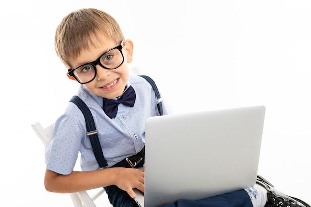 Il ragazzo di scuola dell'adolescente fa i compiti con il computer portatile, isolato