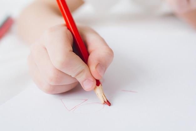 Il ragazzo disegna con le matite colorate che si siedono sul letto