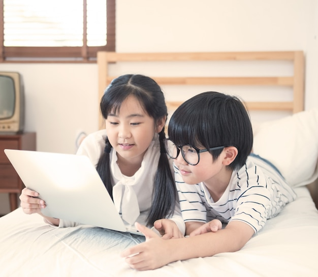Il ragazzo e la ragazza asiatici felici che giocano il gioco in computer portatile che si trova sul letto in camera da letto in casa, il fratello e la sorella che per mezzo del taccuino fanno il compito, concetto di istruzione.