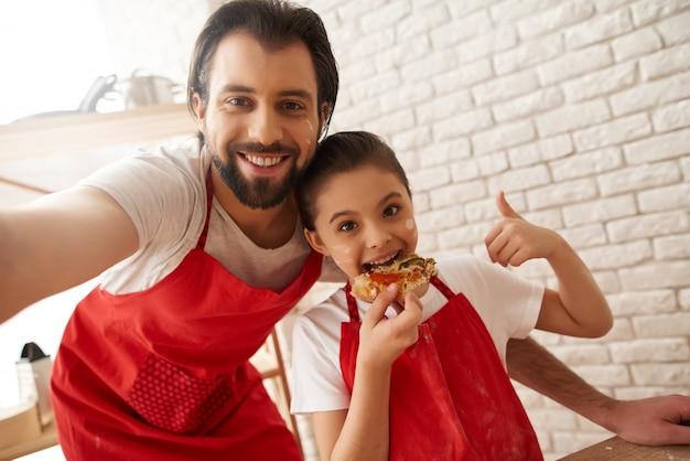 Il ragazzo e la ragazza barbuti in grembiuli rossi stanno facendo la foto di famiglia.